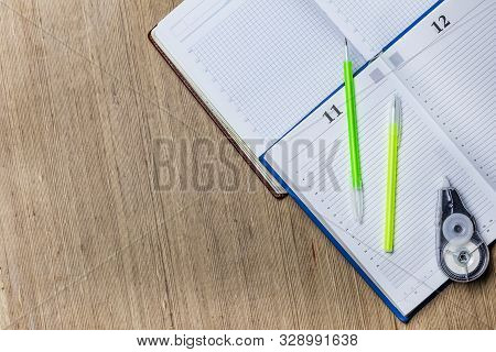 Wooden Background. Handle Them 2 Pieces. And Corrector To Correct Errors. A Diary For Planning Work