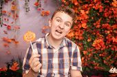 angry disgruntled teenager in plaid shirt sits with pumpkin Lollipop and shows an evil face against the background of autumn leaves. the child is dissatisfied with the result of trick or treat poster