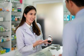 Confident Asian Young Female Pharmacist With A Lovely Friendly Smile And Explaining Medicine To Her