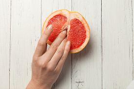 Two Female Fingers In Grapefruit, Woman Masturbation And Sex Concept. Vagina And Clitoris Symbol.
