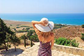 Portrait Of Beautiful Woman Wearing Wide Straw Hat Looking To The Sea Side