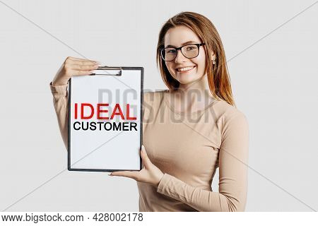 Ideal Customer. Beautiful Young Business Woman Wearing Glasses Holds A Clipboard With Mock Up Space