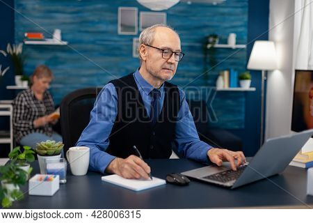 Portrait Of Mature Man Doing Websurfing On Laptop From Home Office. Elderly Man Entrepreneur In Home