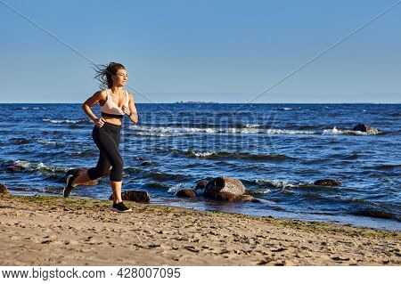 White Woman 30 Years Old Runs On Beach At Daytime.