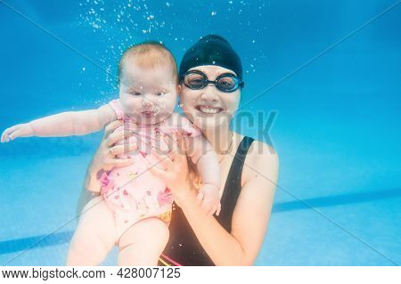 Young Mother, Swimming Instructor And Happy Little Girl In The Pool Swimming Under Water. Teaches In