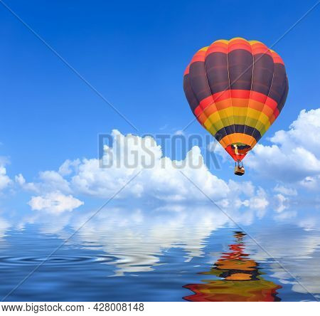 Colorful Hot Air Balloons In Flight Over Blue Sky With Water Reflection