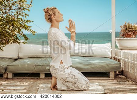 Nice Calm Female Doing Yoga Exercises on the Terrace of the Beach House. Meditating on the Beach. Soul Harmony. Peaceful Summer Vacation.