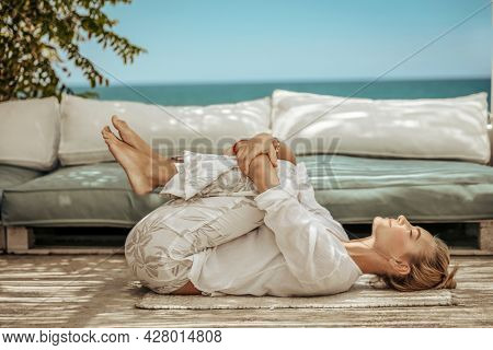 Nice Calm Female Doing Yoga Exercises on the Terrace of the Beach House. Meditating on the Beach. Zen Balance. Peace and Relaxation Concept.