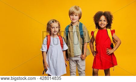 Three Children Of Students With School Backpacks On A Yellow Background. Different Ethnic Groups Of