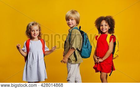 Three Children Of Students With School Backpacks. Different Ethnic Group Of Kids Go Back To School T