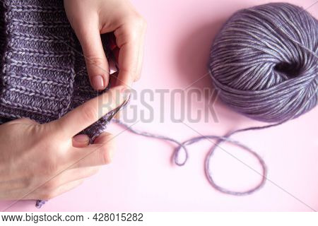 Female Hands With Knitting Needles To Knit Wool Violet Sweater And Tangle Of Woolen Thread On Pink B