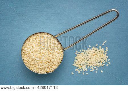 white sesame seeds in a metal measuring scoop  against blue handmade paper