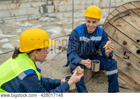 Two builders in hardhats and workwear having sandwiches with tea at lunch break