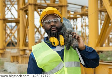 Portrait of African construction worker in work helmet looking at camera while working with drill on construction