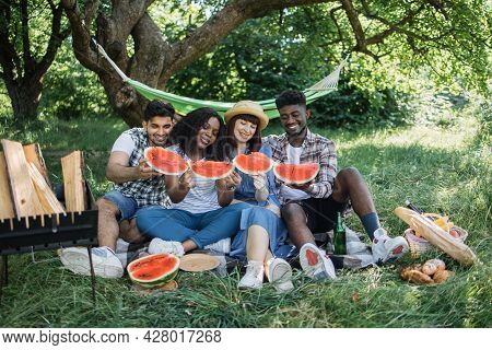 Positive Multicultural Friends Eating Sweet Watermelon During Picnic Time On Nature. Four Young Peop