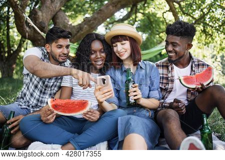 Group Of Young Diverse Friends In Casual Clothes Sitting Together At Green Garden And Looking On Sma