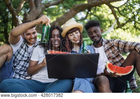 Group Of Four Multi Ethnic People Using Wireless Laptop For Video Conversation Outdoors. Happy Frien