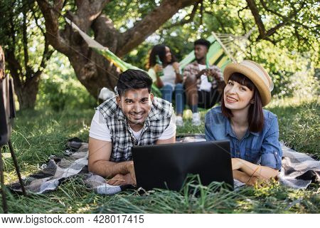 Smiling Diverse Couple Using Modern Laptop While Relaxing Together On Blanket At Garden. Blur Backgr