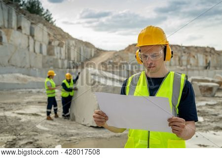 Young serious foreman in protective workwear looking at sketch on blueprint