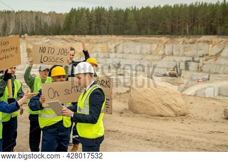 Foreman with tablet showing working requirements to dissatisfied builders with placards