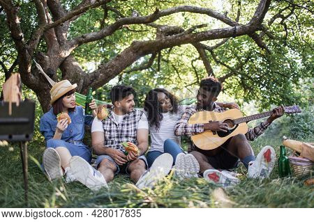 Carefree Diverse People Sitting At Summer Garden With Fast Food And Drinking, And Playing Guitar. Fo