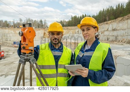 Intercultural colleagues in workwear and hardhats standing by total station