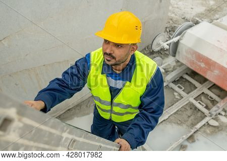 Young mixed-race builder in workwear going to climb upwards on stepladder