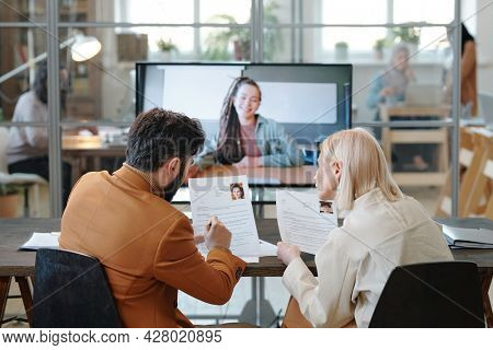 Two employers consulting about resume of female applicant on large display after online interview