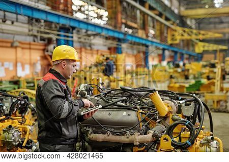 Portrait of mature engineer in workwear looking at camera working in machine factory