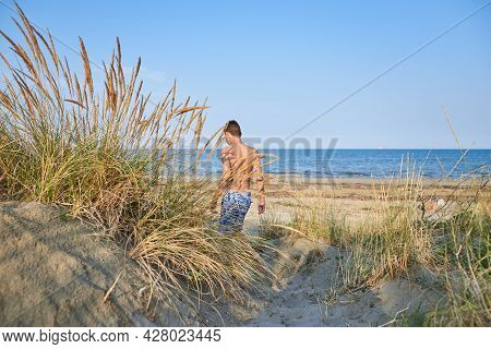 Traveler boy on beach in vacation.Young boy relaxing in vacation. Boys on beach in vacation. Boy in vacation relaxes on beach in summer day. Traveler. Summer. Vacations.