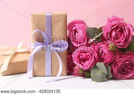 Gift And Flowers On A Colored Background. Holiday, Give A Gift, Congratulations