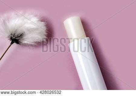 Close Up Of Hygienic Lip Balm And Fluffy White Flower On Pink Background.