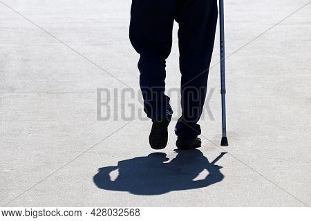 Silhouette Of Man Walking With A Cane Down The Street, Shadow On Asphalt. Concept Of Old Age, Diseas