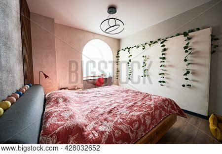 Side View Of Bright Bedroom With Modern Furniture And Trendy Lamps And Good Light From Window. Conce