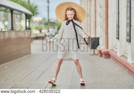 Kid's fashion. Full length portrait of a beautiful girl child in elegant wide-brimmed straw hat and polka-dot dress posing on a city street.