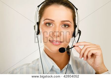 Close-up of young customer service girl with a headset isolated on white background