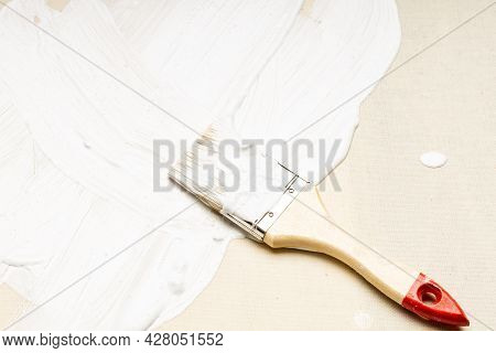 The Canvas Is Covered With Half White Paint, Next To It Is A Brush With A Wooden Handle. Painting On