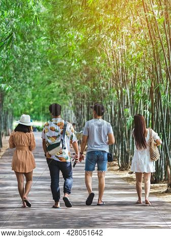 Group Of Asian Friends Walking On Pathway Through Bamboo Garden. Cheerful Group Of Friends Having Fu