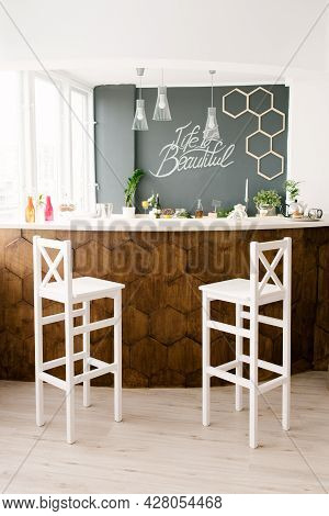 A Stylish Modern Bar Counter Decorated With Wooden Tiles And Two White Bar Stools In The Living Room