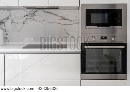 Modern Kitchen Equipment Built In White Furniture. Induction Cooking Panel Or Electical Plate On Cou