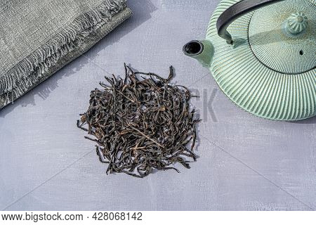 Dried Organic Black Tea Leaves On Gray Background. Composition With Iron Teapot And Linen Cloth. Asi
