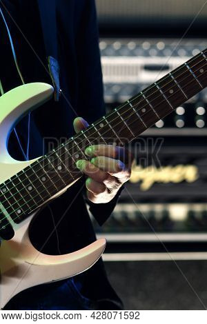 Fingers Of Musician Are Pressing Strings On Electric Guitar. Closeup Hand Of Musician Playing Guitar