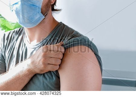 Hands Of Doctor Injecting Coronavirus Covid-19 Vaccine In Vaccine Syringe To Arm Muscle Of Caucasian
