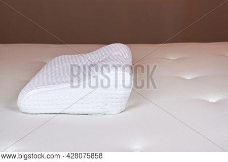 White Orthopedic Pillow On A White Mattress. Orthopedic Pillow With Memory Effect. Orthopedics, Heal