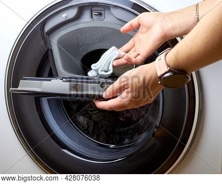 Function Adding Laundry During Washing. A Person Puts Clothes In The Washing Machine. The Flap In Th
