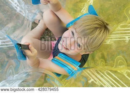 A Child In A Bumperball. Portrait Of A Happy Laughing Child. Happiness, Fun And Laughter