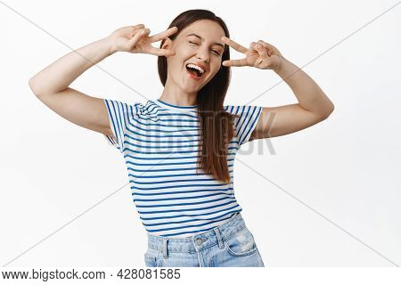 Positive Smiling Brunette Girl Shows Peace V-sign, Laughing, Winking And Looking Carefree, Positivit