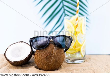 Coconut With Sunglasses On The Beach Sand. Fruit In Trendy Sunglasses.