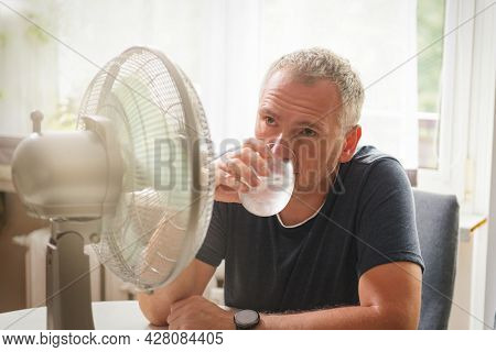 Man suffers from heat at home drinking cold water or other drink and tries to cool off by the fan