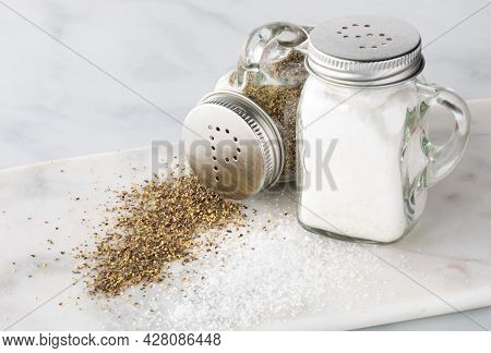 Close Up Of Salt And Pepper Shakers With Salt And Pepper Spilled Out In Front And The Pepper Tipped